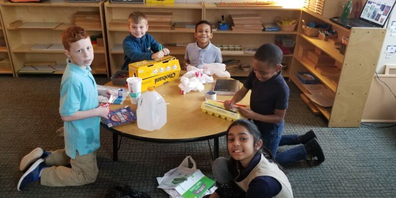 kids smiling at school table making crafts