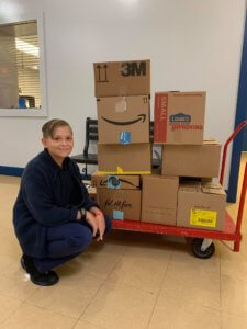 boy next to a cart of cardboard boxes